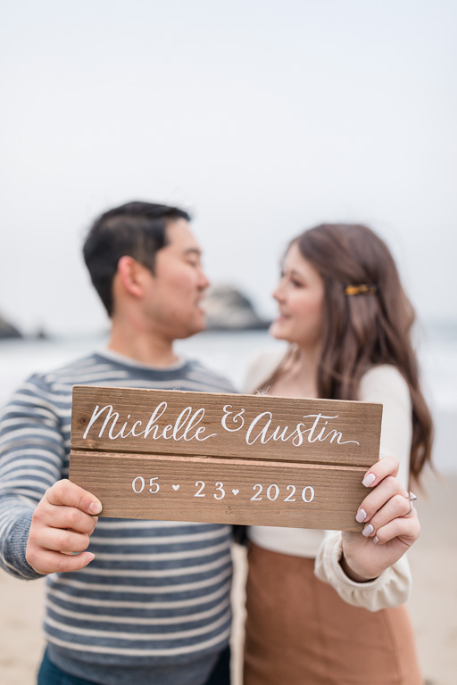 a pretty calligraphy wooden save-the-date sign their friend did for them