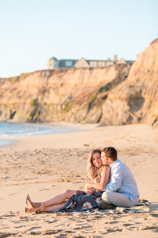 couple snuggle on the golden soft sand beach in Half Moon Bay