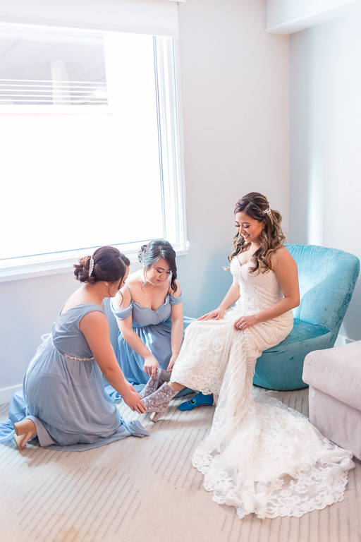 bridesmaids helping the bride to put on her boots