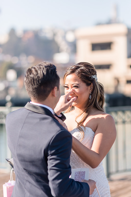 groom wiping bride's happy tears at their first look at downtown San Francisco
