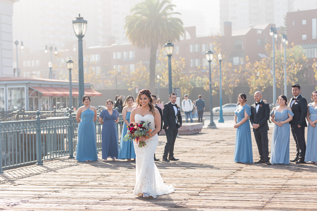 bride walking towards her groom from behind with bridal party watching
