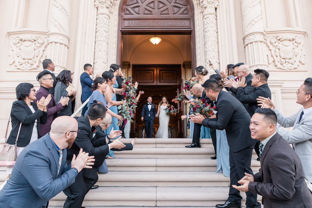 friends and family lining up for the groom and bride to exit Mission Dolores Basilica
