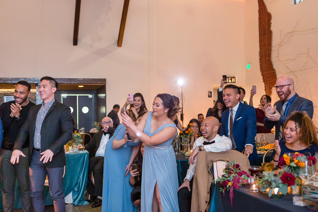 happy wedding guests taking video of the epic moment