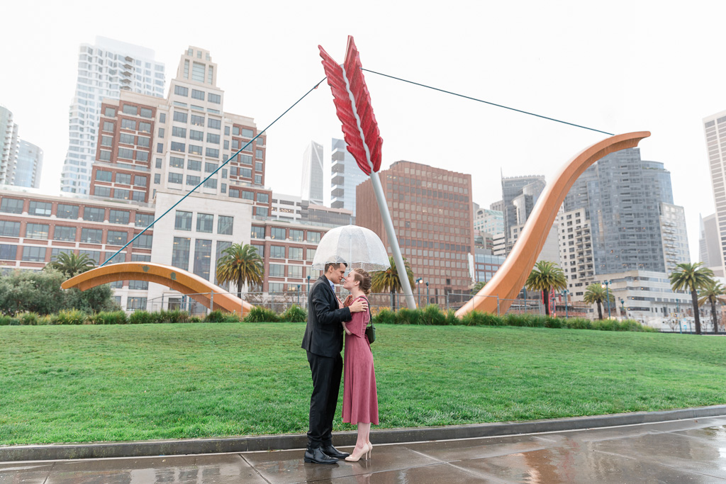 cute engagement photo in the rain with clear umbrella at Cupid's Span