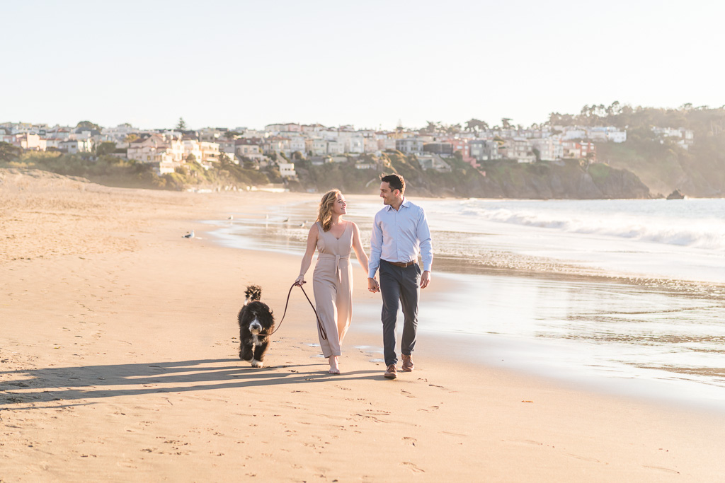couple walking with their dog on Baker Beach