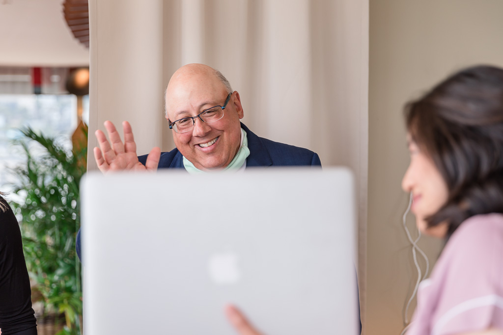 father of the bride waving at the bridesmaids on computer screen