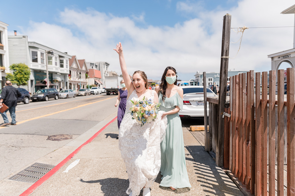 excited bride waving to people on the street