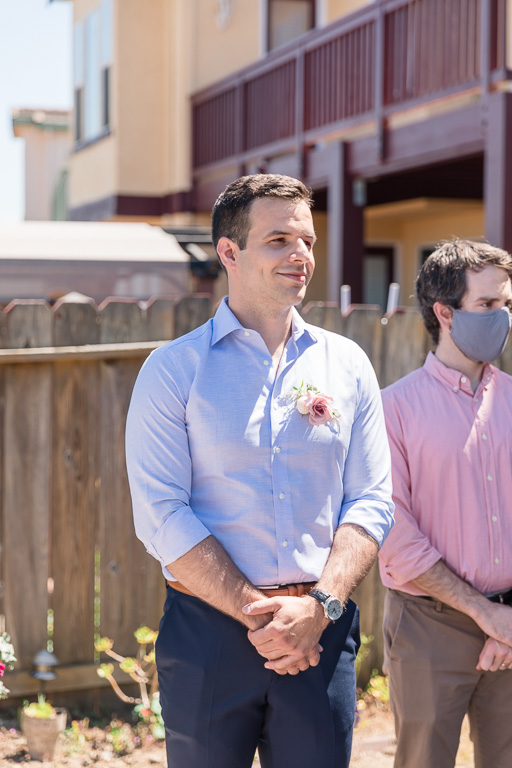 groom at backyard wedding looking at bride coming down aisle
