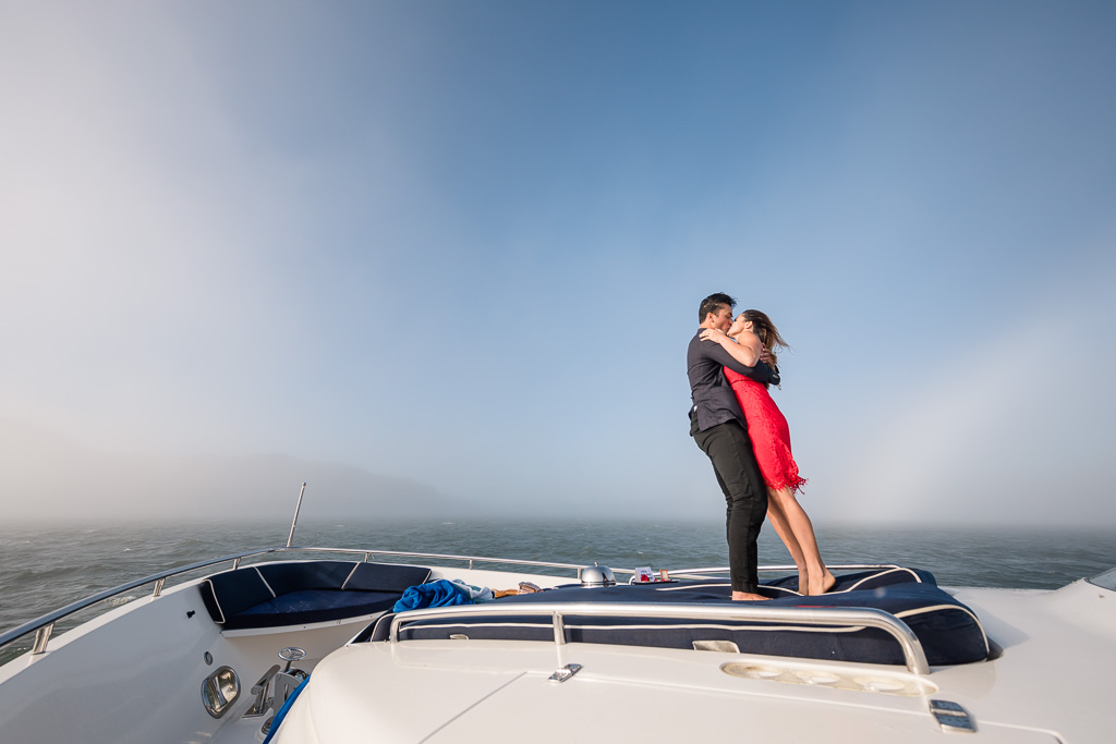 standing and kissing on the bow of a yacht in the San Francisco bay