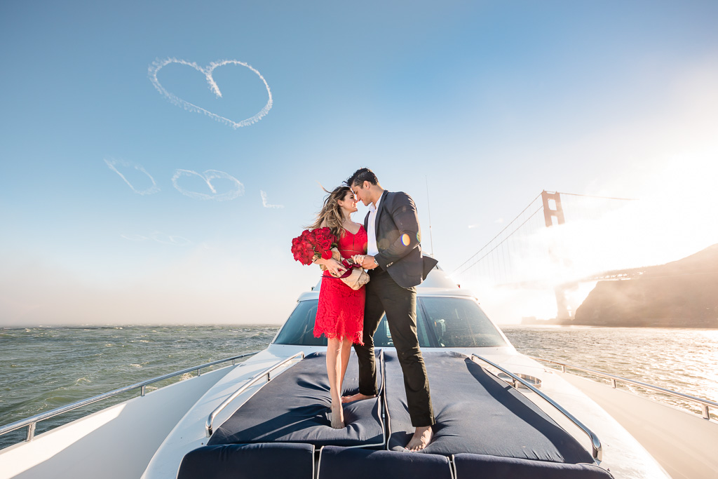 engagement photo on a yacht with heart skywriting over the Golden Gate Bridge