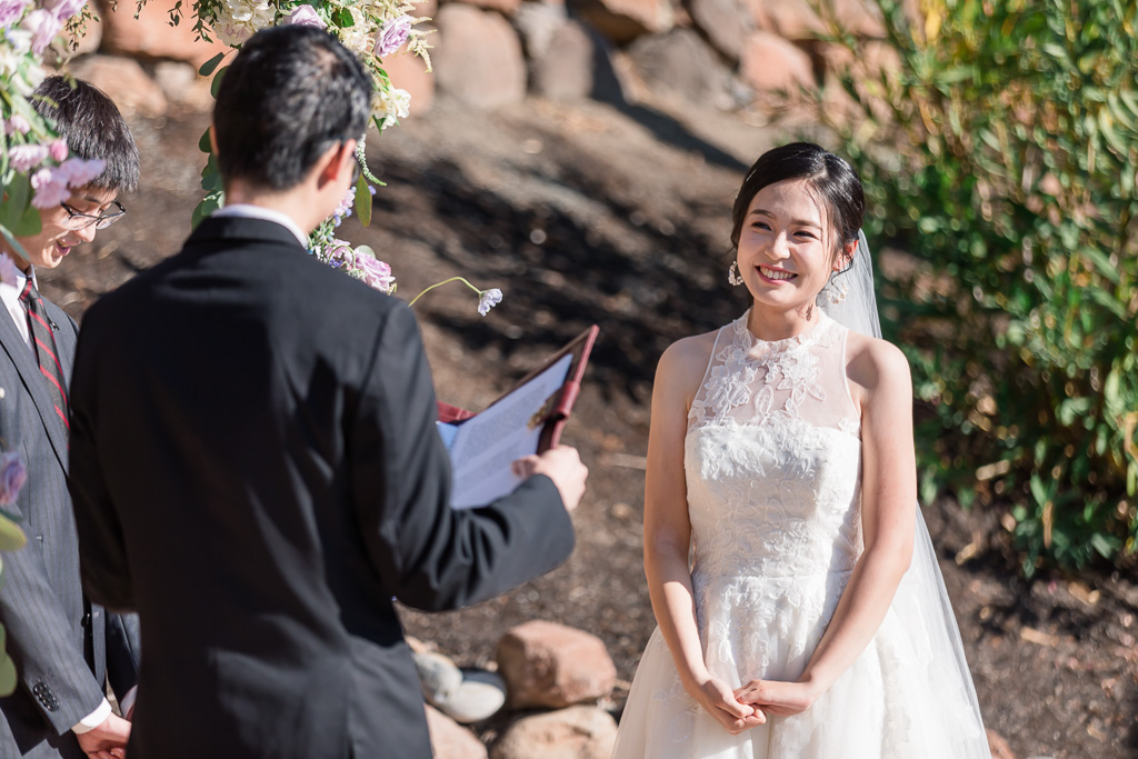 bride smiling at groom reading his marriage vows