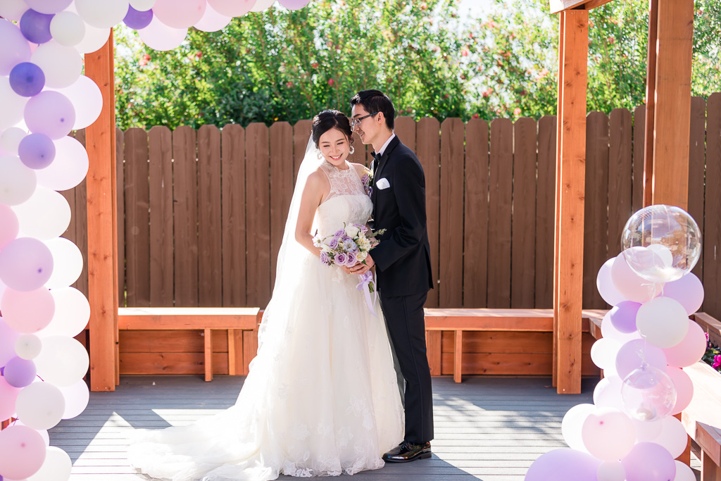 portrait of bride and groom with purple balloons