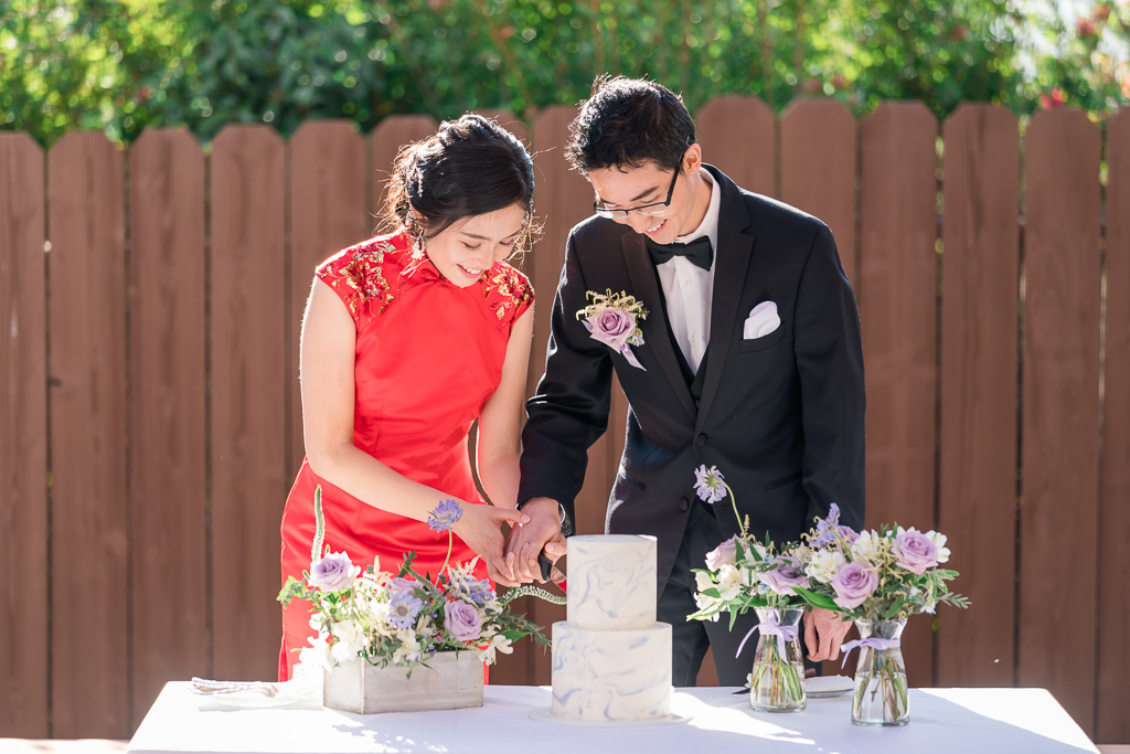 bride and groom cutting cake in traditional qipao dress
