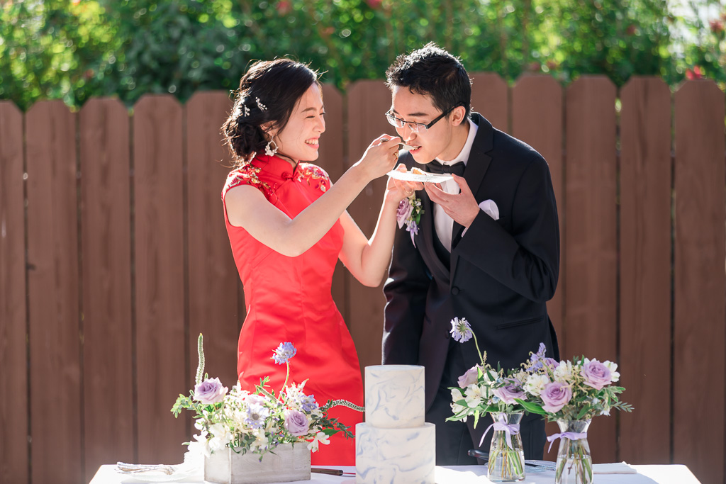 bride laughing and feeding groom cake