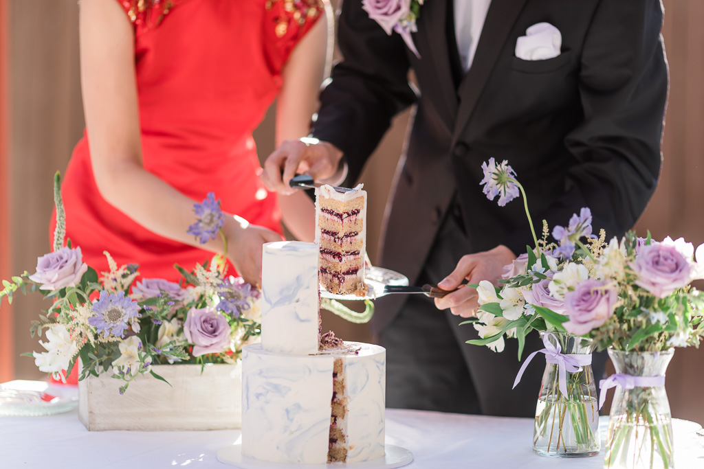 groom cutting out a very professional, neat, nearly equilateral triangle cake slice