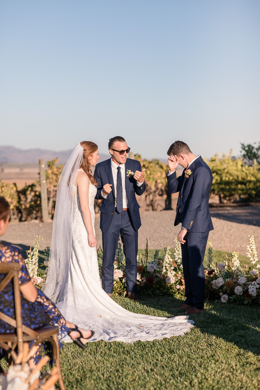 groom wiping off a tear during wedding ceremony