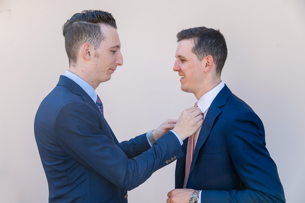 groom's brother helping him with his tie