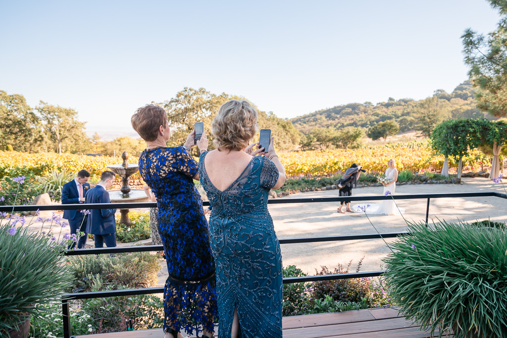 two moms taking photos of the bride on her wedding day
