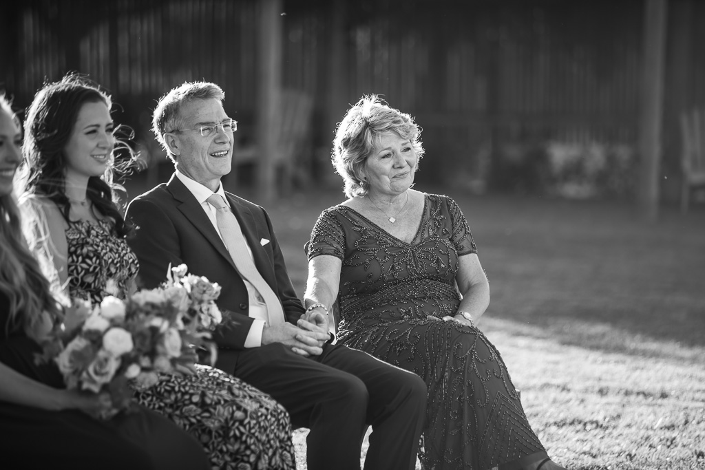 black and white photo of the bride's parents during ceremony