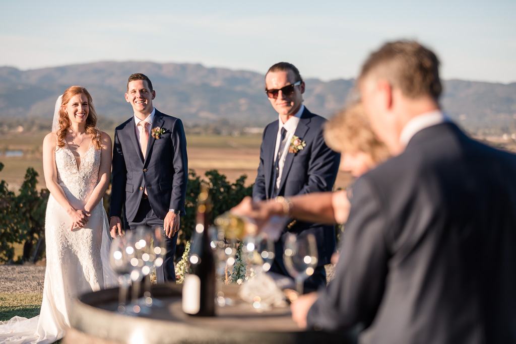 bride and groom watching wine pouring ceremony