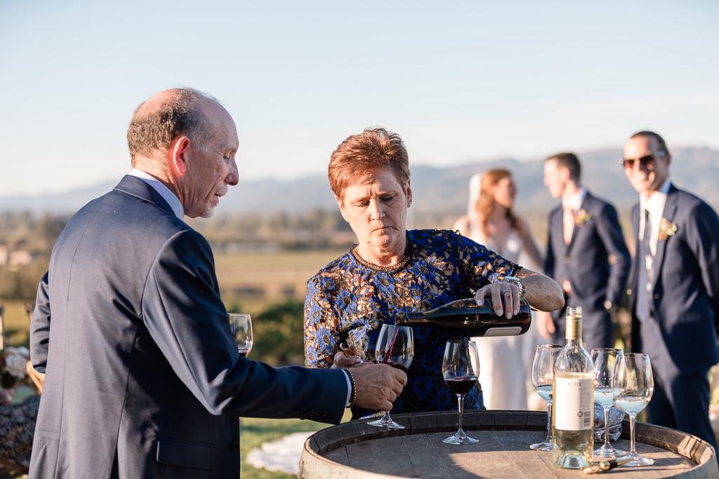 parents of the groom pouring wine during wedding ceremony