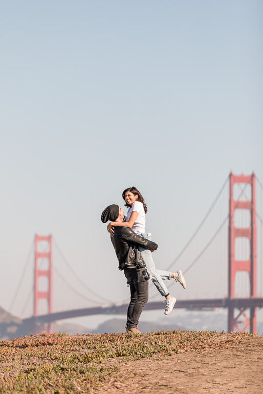 girl being lifted up in front of the Golden Gate Bridge