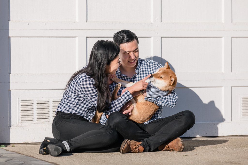 couple playing with their new puppy outside their house