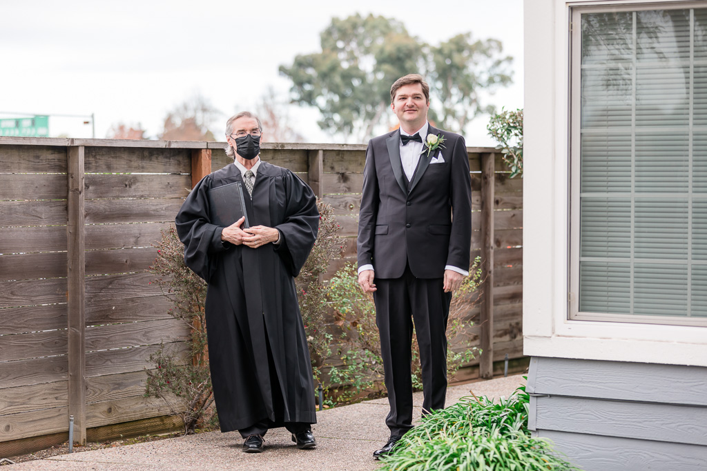 priest and groom entering backyard ceremony