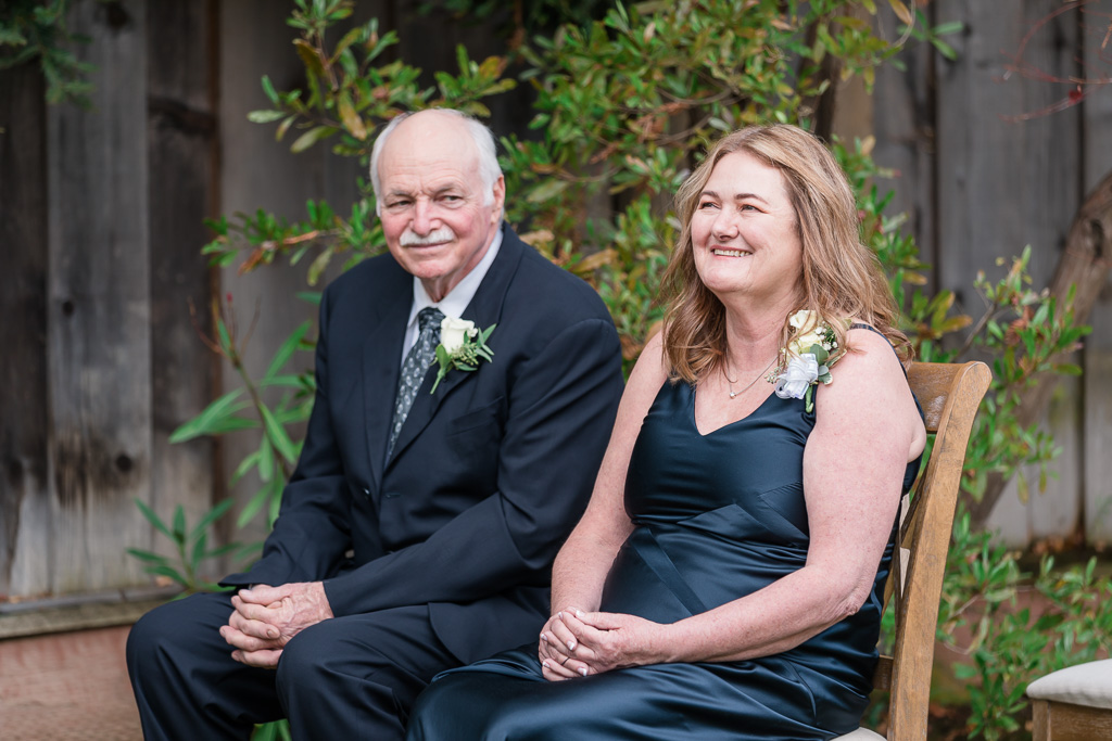 parents in the first row during intimate backyard ceremony