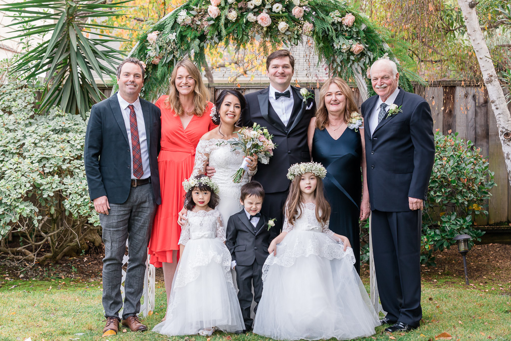 photo of entire family in front of floral wedding arch