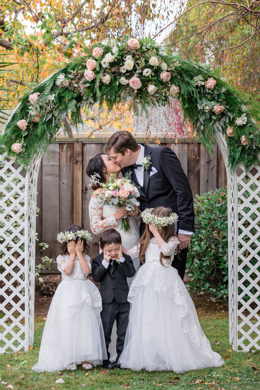 cute family photo with kids in front of wedding arbor arch