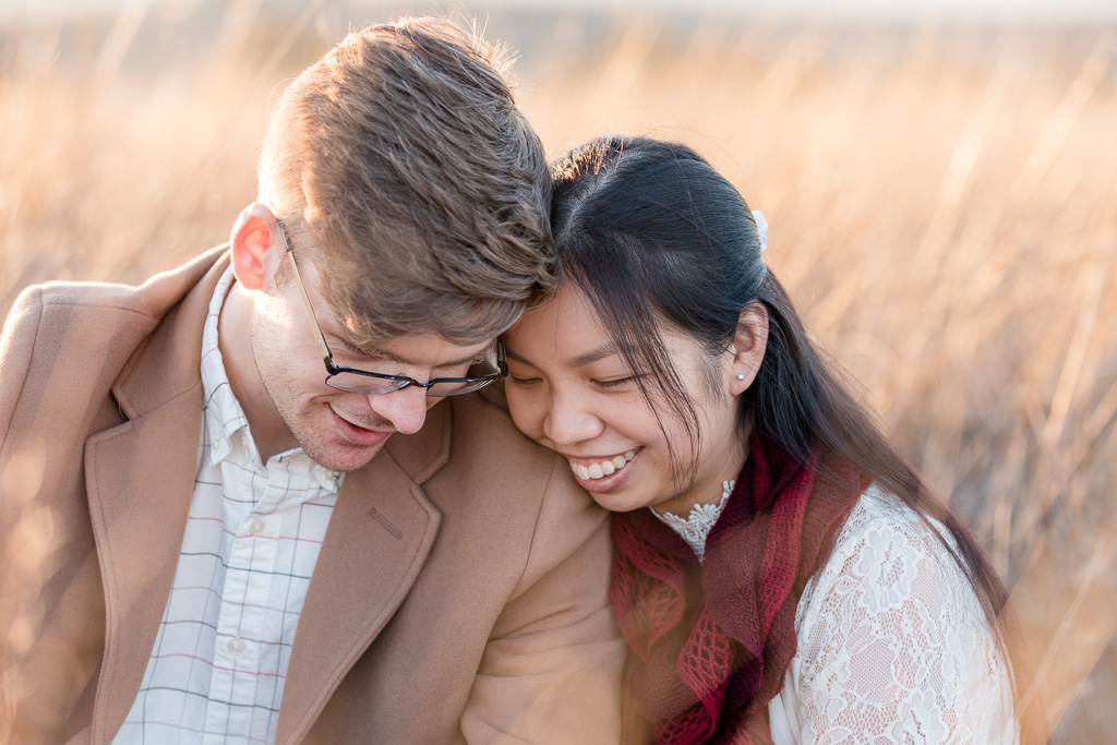 engaged couple snuggling in tall golden grass