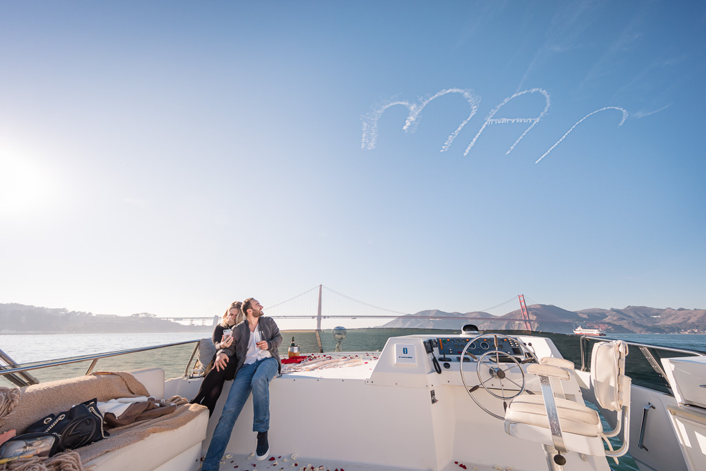 newly engaged couple sitting under marry me written in the sky in huge letters