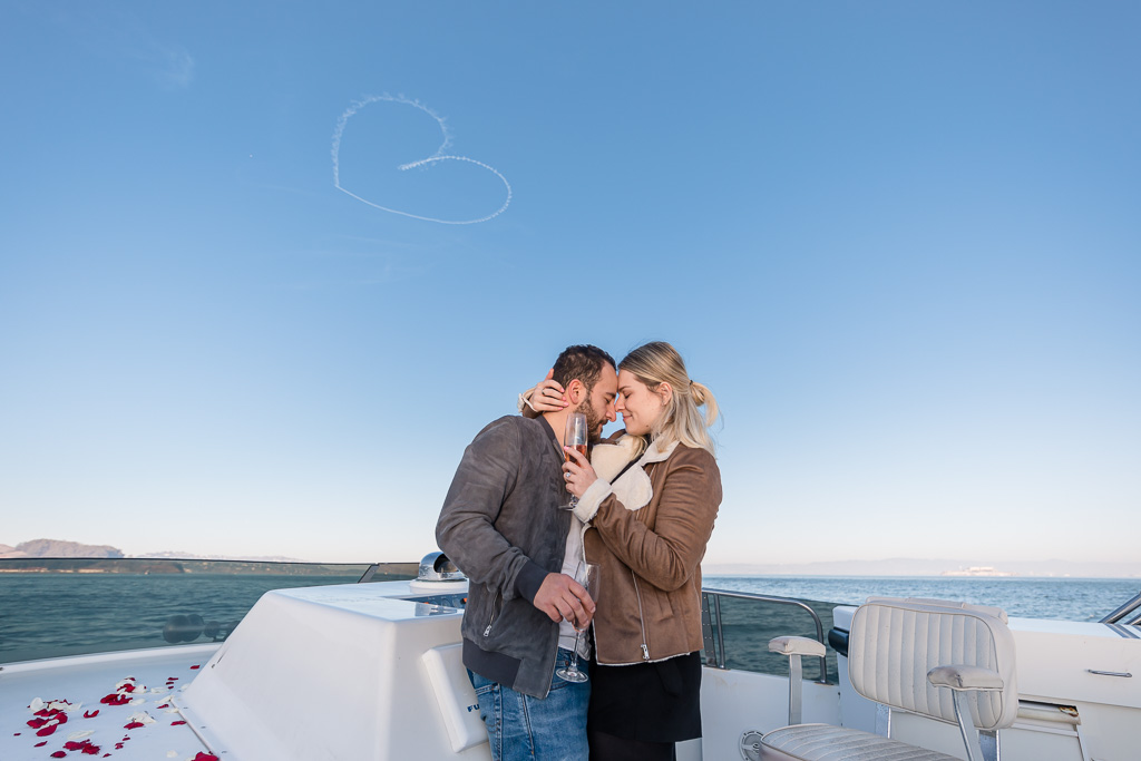 couple on a yacht under a huge heart drawn in the sky by airplane pilot