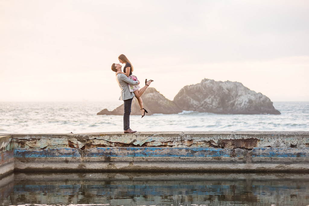 girl being picked up for engagement photo