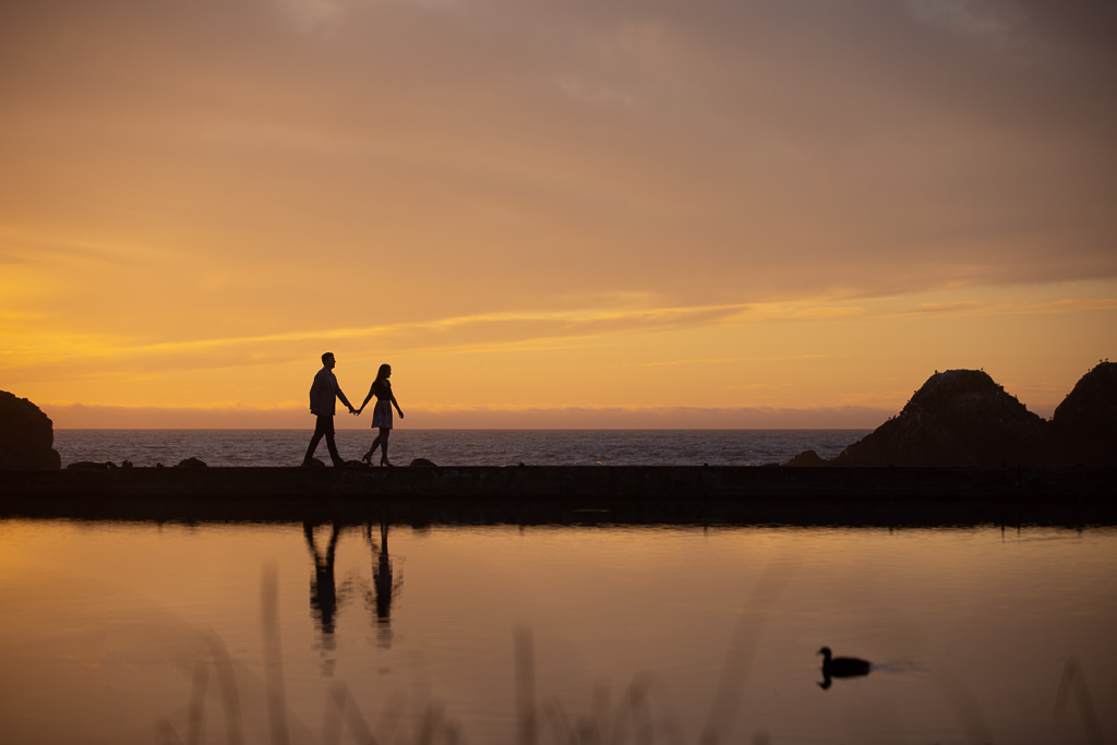 Sutro Baths sunset silhouette engagement picture of couple walking along the water