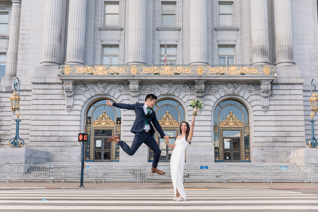 groom jumping for joy in front of San Francisco City Hall