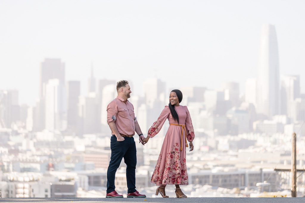 couple engagement photo in front of San Francisco skyline