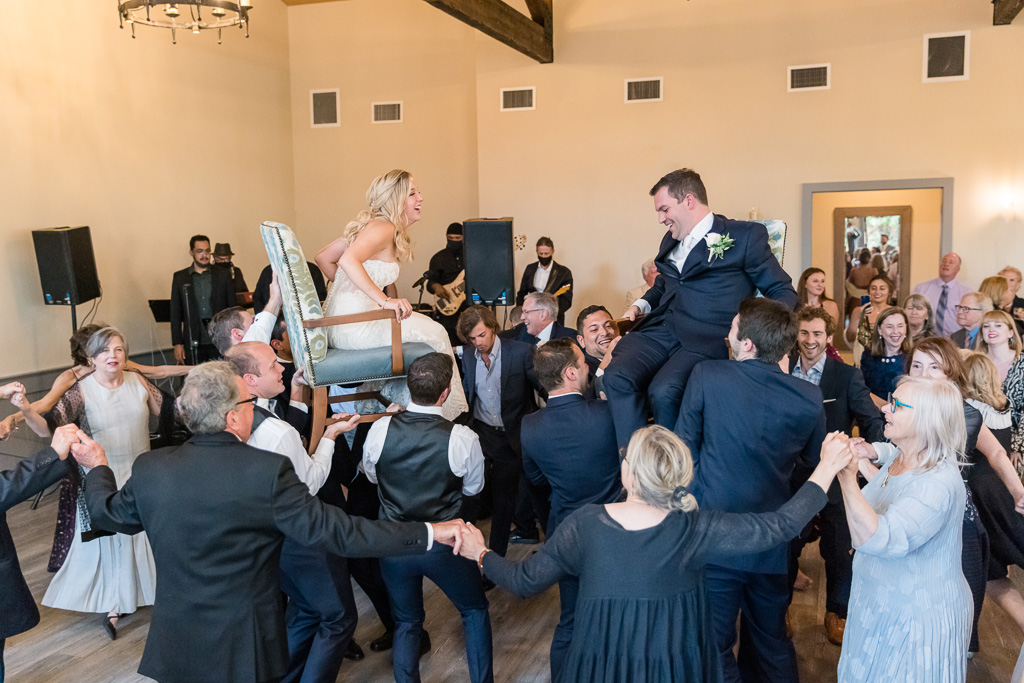 bride and groom lifted up in chairs during wedding reception
