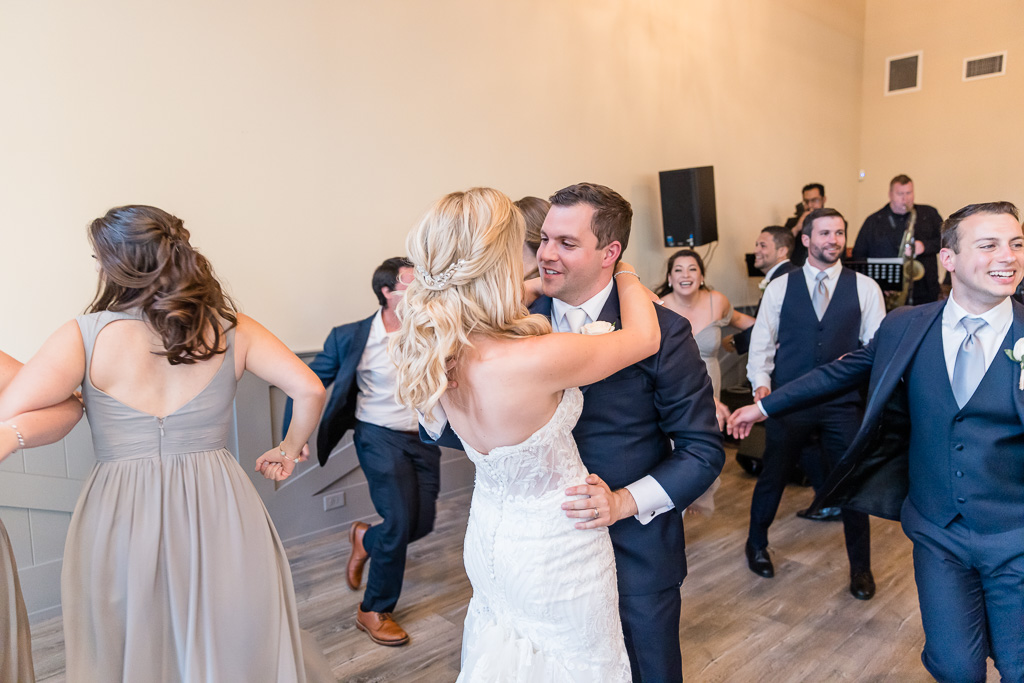 bride and groom sharing a dance with guests surrounding them