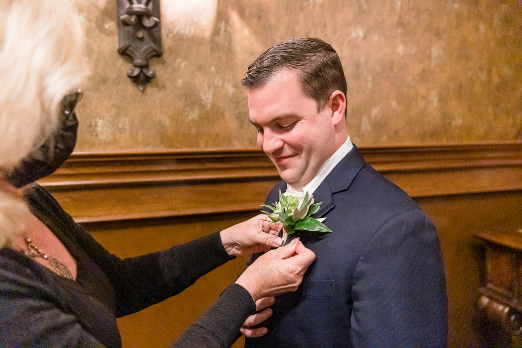 groom getting boutonniere pinned