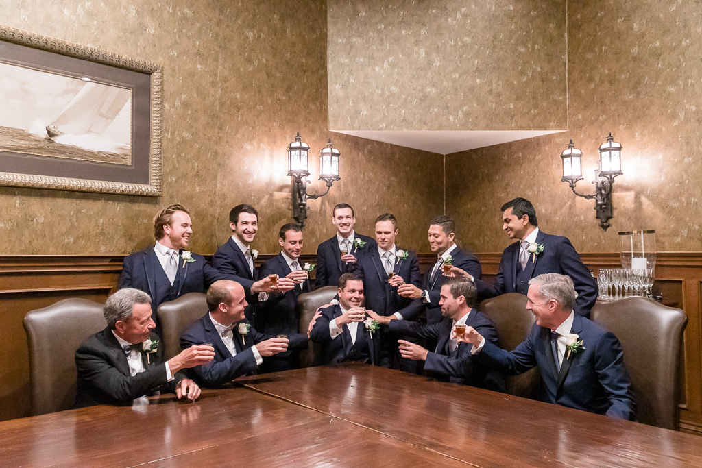 groom and groomsmen taking a shot of courage before wedding ceremony