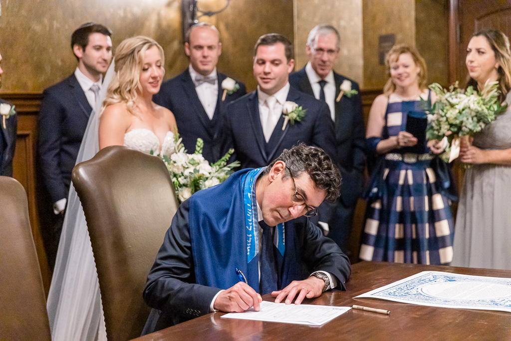 rabbi signing marriage document while bride and groom look on