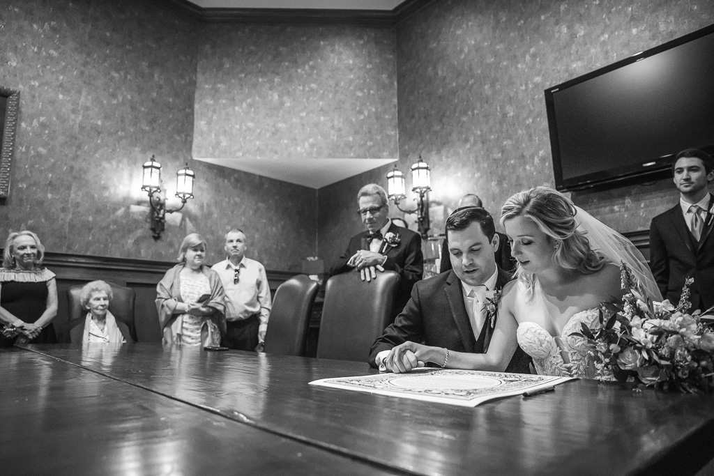 bride and groom reading the ketubah