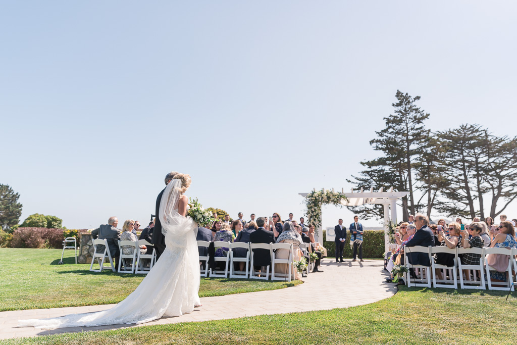 grand photo of bride and father walknig down the aisle at Oceano Hotel, showing bride's full dress train