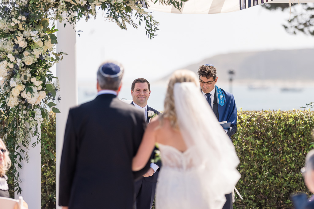groom reacting to bride walking down the aisle during wedding ceremony