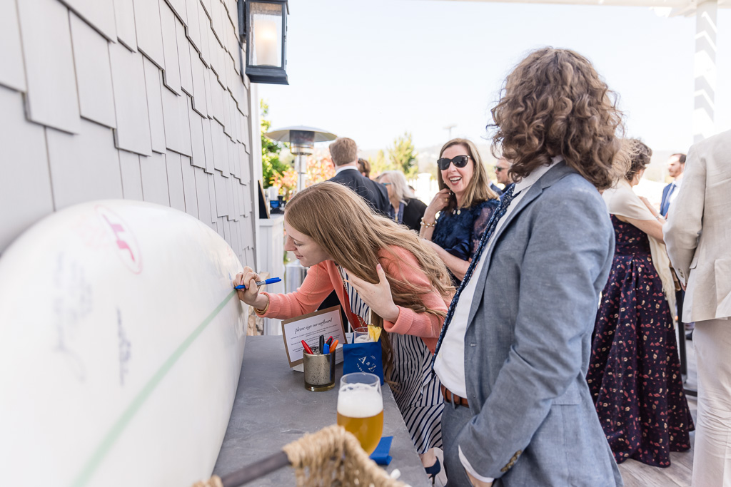 wedding guests signing a surfboard