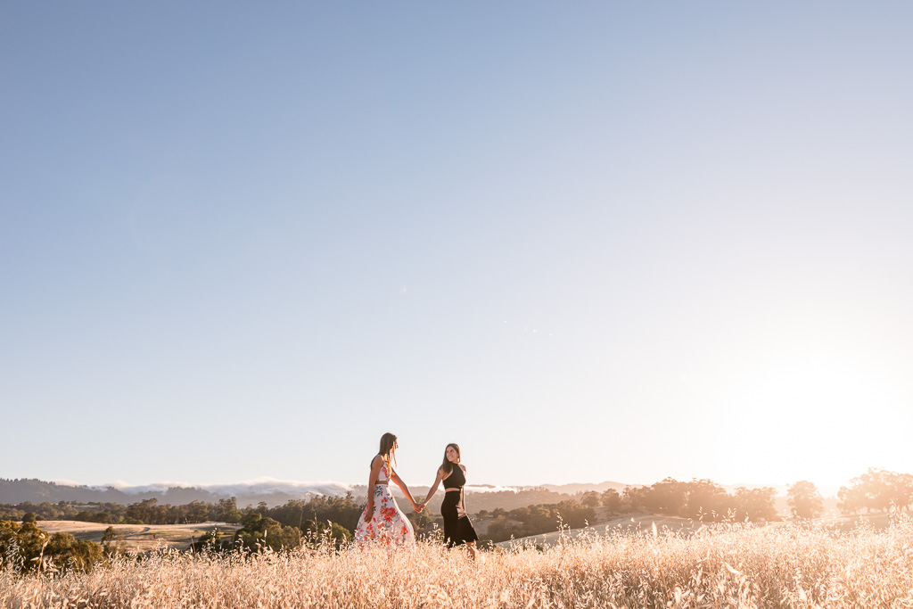 engagement photo of couple walking in rolling grassy hills
