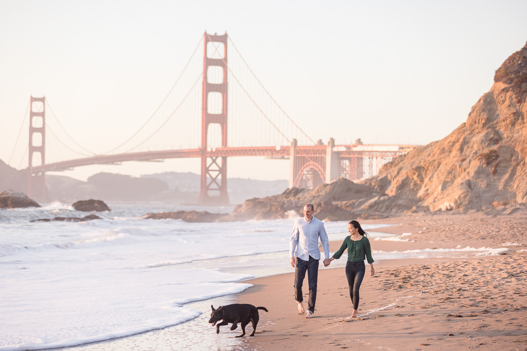 couple walking their dog on the beach in front of the Golden Gate Bridge