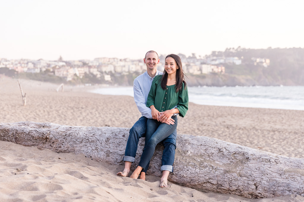 couple sitting on a log at the beach